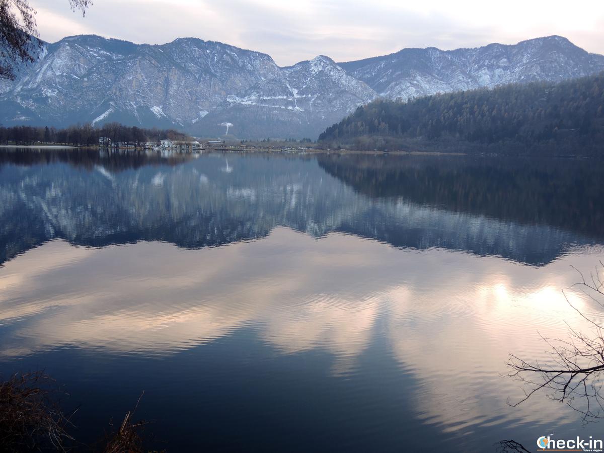 I monti innevati si specchiano sul lago di Levico Terme